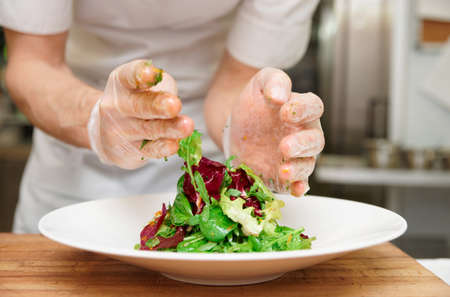 food hygiene: Chef is making an appetizer at professional kitchen