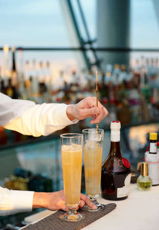 stirring: Bartender is stirring a cocktail, sunset light Stock Photo