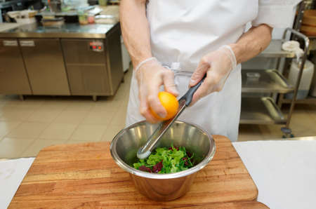 Chef is zesting orange in bowl with salad at commercial kitchen  photo