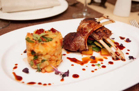 drizzle: Grilled rack of lamb with potatoes and vegetables on restaurant table