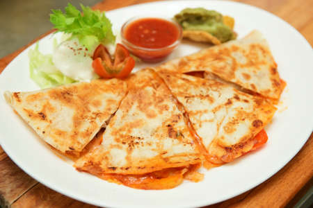 Quesadilla in plate on wooden plank