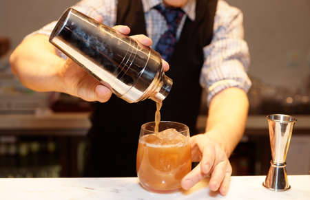 cocktail shakers: Bartender is making cocktail at bar counter