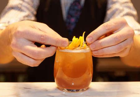 Barman is decorating cocktail with lemon zest Foto de archivo