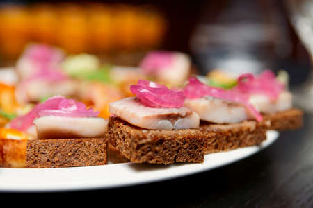 Herring canapes with onion  in plate, close-up, shallow focus photo