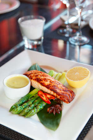 Asian style salmon steak on restaurant table photo