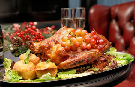 Roasted turkey with baked apples and grapes, festive dish photo