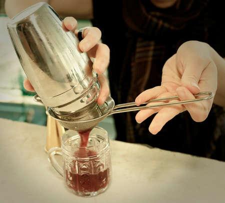 straining: Bartender is straining cocktail into jar glass