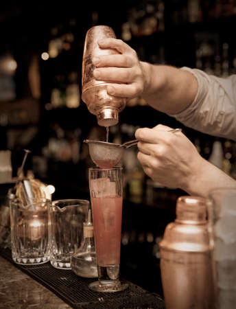 Bartender is straining cocktail in highball glass photo