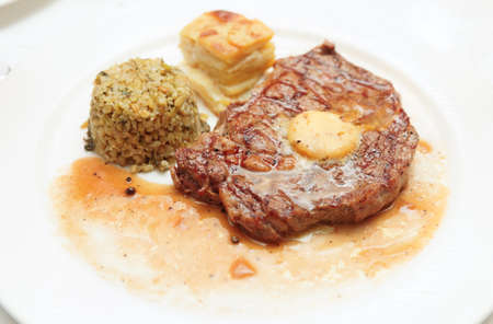 rib eye: Rib eye steak with bulgur, butter and potato gratin on plate Stock Photo