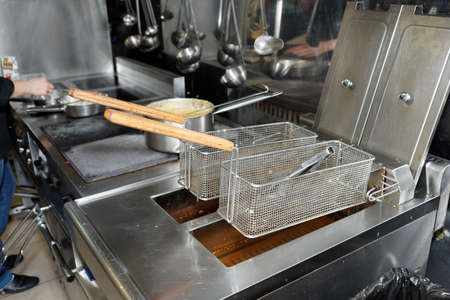 Deep fryers with boiling oil on fast food kitchen  Standard-Bild