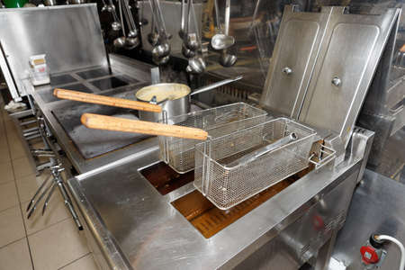 Deep fryers with oil on kitchen photo