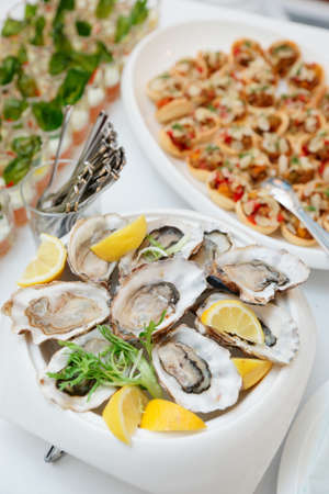 Fresh oysters and another dishes on restaurant table photo