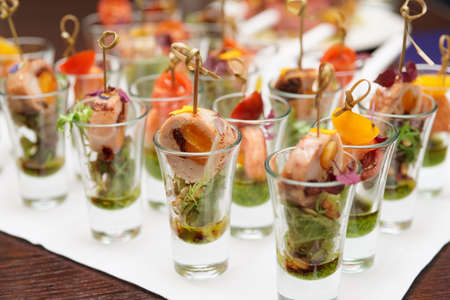 Various snacks in shot glasses, close-up