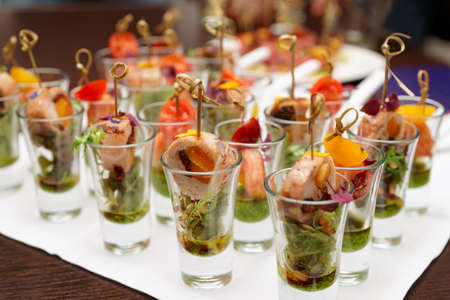 buffet table: Various snacks in shot glasses on table