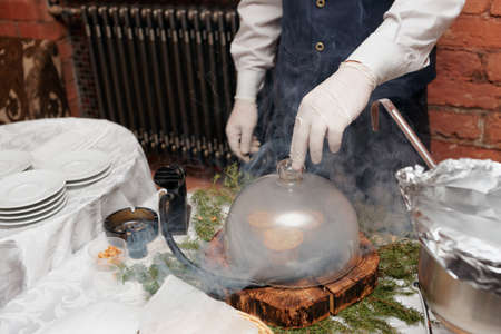 Chef is smoking a dish before serving, modern cooking technique photo