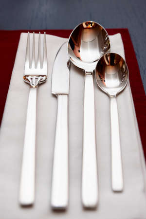 Fork, knife, spoons and napkin on restaurant table photo