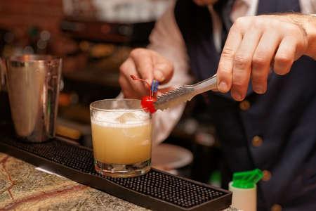 Barman versieren whisky cocktail met kersen