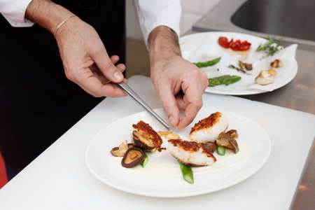 coalfish: Chef is cooking a fish dish with vegetables and mushrooms