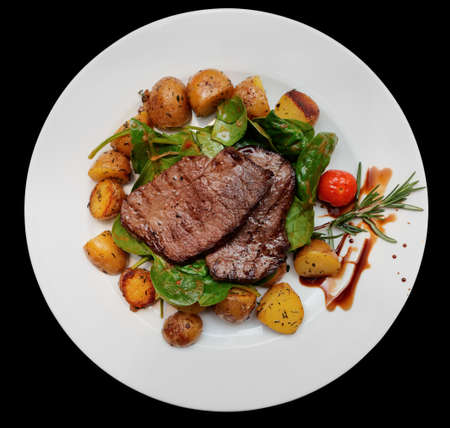 fat food: Steak with fried potatoes and spinack on wooden table  Stock Photo