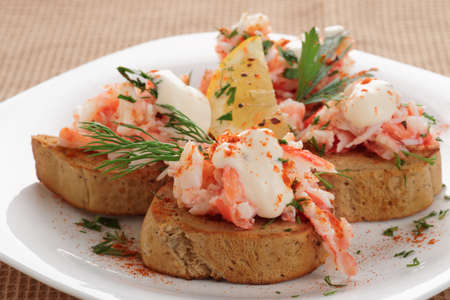 fine legs: Crab meat with toast, sauce and  herbs on plate Stock Photo