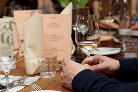 winetasting: Glass of white wine in mans hands during a dinner Stock Photo