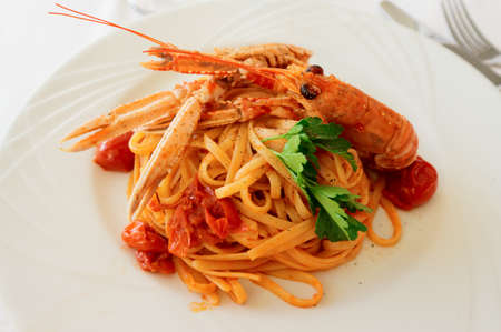 Pasta with tomato sauce and langoustines, close-up photo