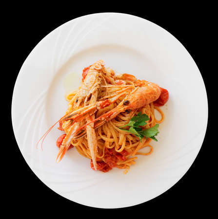 Pasta with tomato sauce and langoustines (scampi) isolated on black photo