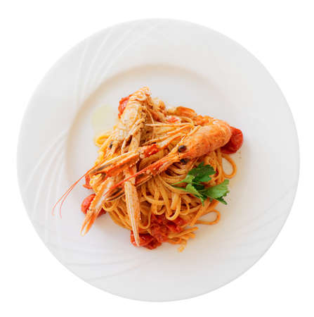 Pasta with tomato sauce and langoustines (scampi) isolated on white photo