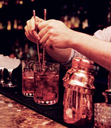Bartender rührt Cocktails in Misch-Gläser