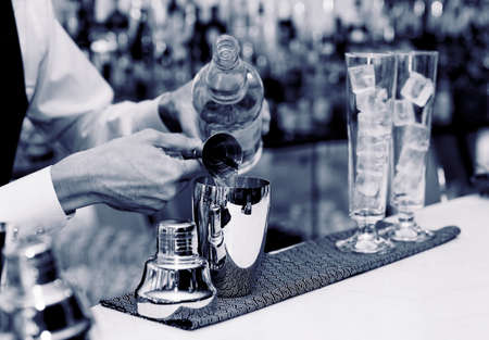 cocktail shaker: Bartender is pouring liquor in golden shaker Stock Photo