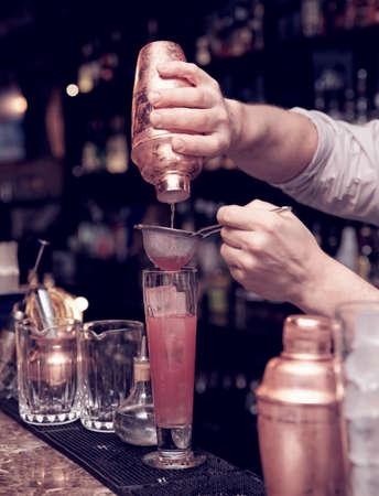 Bartender is straining cocktail in highball glass