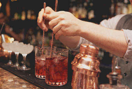 Bartender is stirring cocktails on bar counter 스톡 콘텐츠