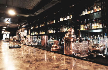 Classic bar counter with bottles in blurred background photo