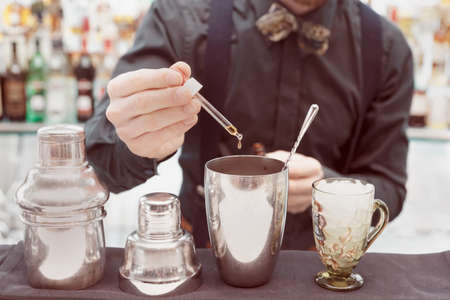 cocktail shaker: Bartender is making cocktail at bar counter, toned