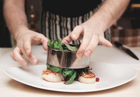 Chef-kok kookt voorgerecht met coquilles, afgezwakt