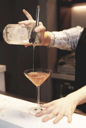 Bartender is making a cocktail, toned