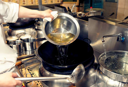 fryer: Chef is pouring cooking oil in wok, toned