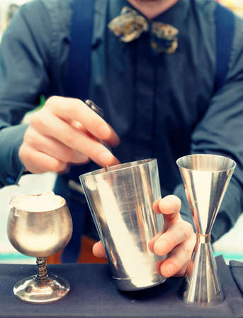 Bartender is stirring a cocktail, toned photo