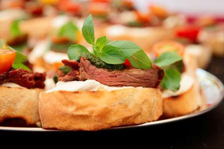 Bruschettas with beefsteak and pesto sauce, close-up photo