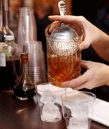 straining: Female bartender is straining cocktail into glass