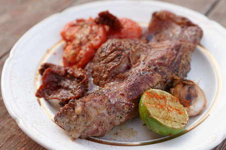 Striploin steak grilled with vegetables, in white plate photo