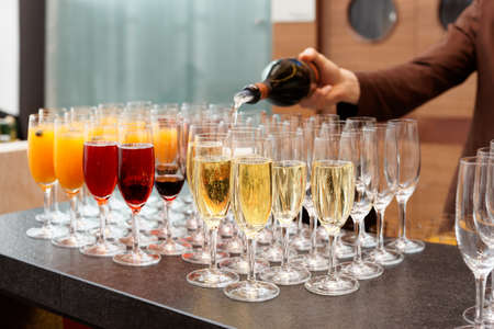 cocktail party: Bartender is pouring sparkling wine in glasses, making cocktails Stock Photo