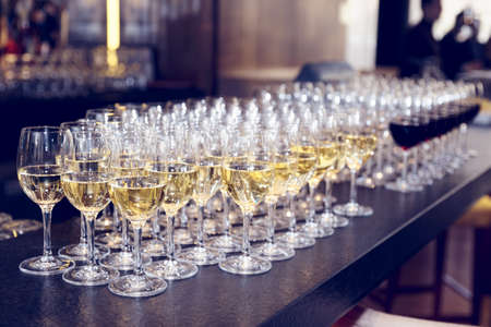 Glasses of white wine on bar counter, small focus depth, toned image photo