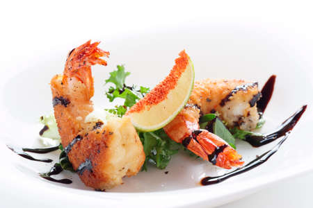 Deep fried shrimps on white plate, light background