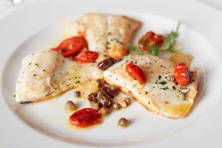 Filete de pescado frito con alcaparras y tomates, de cerca Foto de archivo