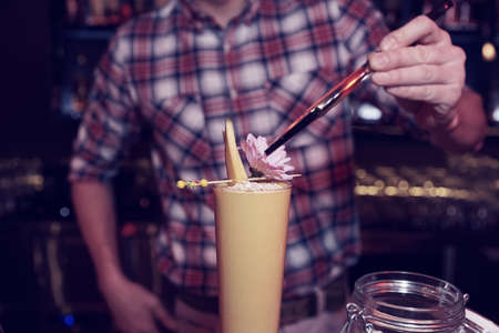 Bartender is decorating a cocktail with mango slices photo