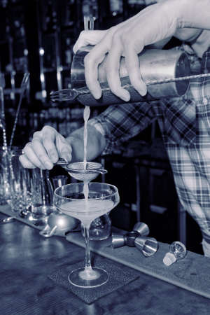 straining: Bartender is straining drink in a glass, toned image