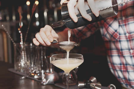 straining: Bartender is straining drink in a glass, toned, misty, bleached colors