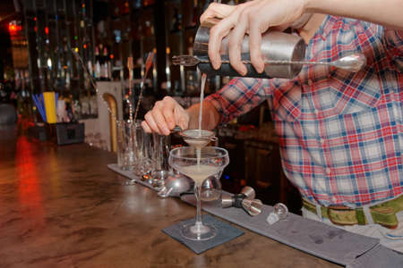 old bar: Bartender is straining cocktail in a glass