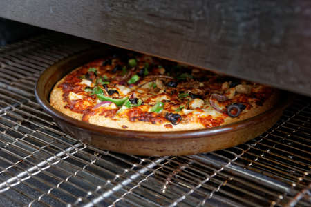Pizza being baked in industrial oven, fast food restaurant Standard-Bild